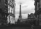small paris street with view on the famous paris eifel tower on a cloudy rainy day with some sunshine - vintage analog black and white photo style poster