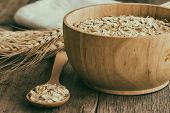 Oat flakes or oatmeal in wood bowl put on rustic wood table. Rolled oat is clean food for health lover people. Prepare oat flakes for bakery or cooking.Natural organic food in vintage style concept.Oat flake, oatmeal background and texture. poster