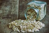 Oat flakes or oatmeal in glass bottle on rustic wood table. Rolled oat is clean food for health lover people. Prepare oat flakes for bakery or cooking.Natural organic food in vintage style concept.Oat flake, oatmeal background and texture. poster