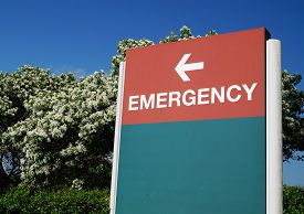 Hospital Emergency Sign. An outdoor green and red sign pointing in the direction of the hospital emergency department