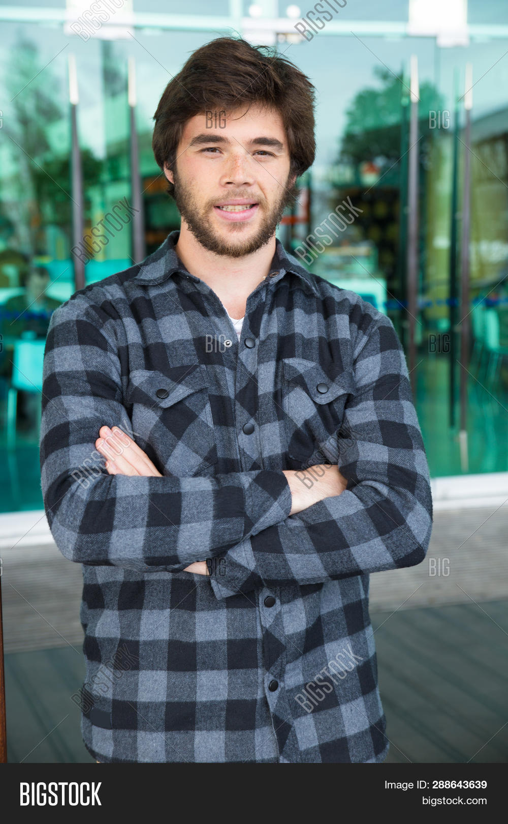 37993a8f Smiling Young Man Standing Outdoors With His Arms Crossed. Handsome Guy  Wearing Casual Shirt,