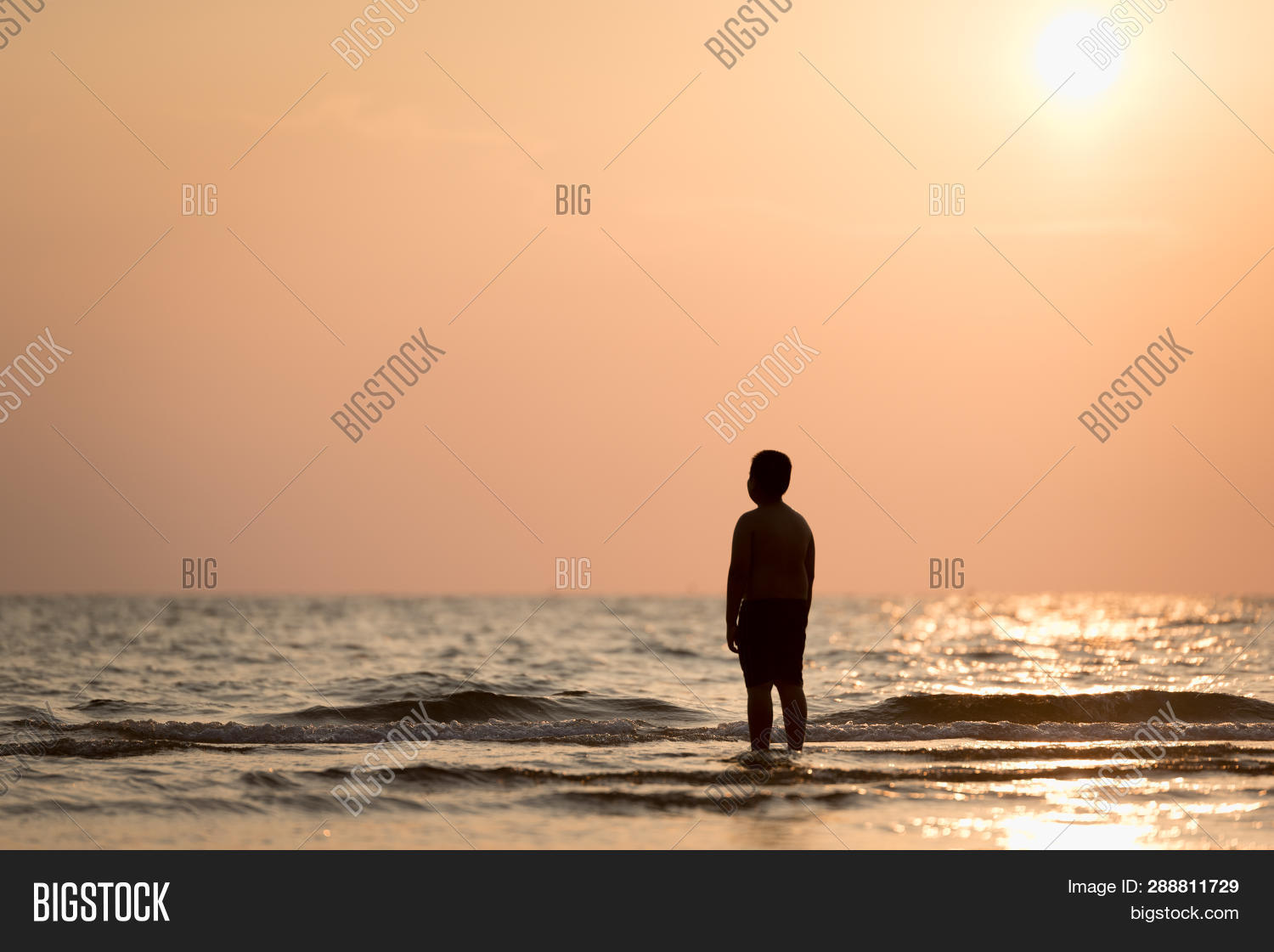 Silhouette of a lonely boy standing alone on the beach at sunset concept of lonely