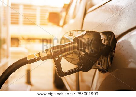 Fuel Nozzle To Refill Fuel In Car At Gas Station. Power Concept.