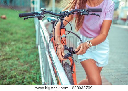 Password Selection For Protection. Girl Locks Bike Parking Lot. Concept Of Protecting Property Thiev