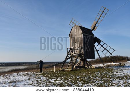 Photographer Shoots A Winter View By An Old Windmill In A Wintry Landscape At The Swedish Island Ola