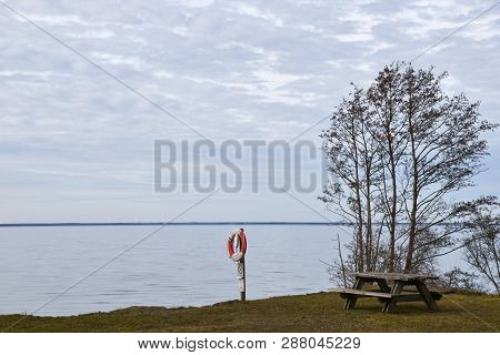 Coastal View From A Resting Place With Lifebuoy And Bench At The Swedish Island Oland In The Baltic
