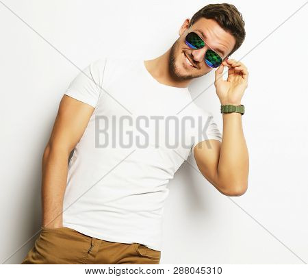 Elegant young handsome manin smart casual wear and sunglasses.