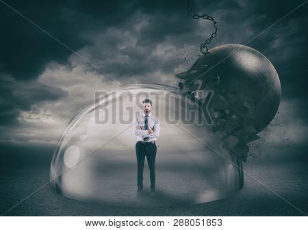 Businessman Safely Inside A Shield Dome During A Storm That Protects Him From A Wrecking Ball. Prote