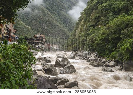 Aguas Calientes Town Landscape With Powerful Urubamaba River On Foreground In Peru