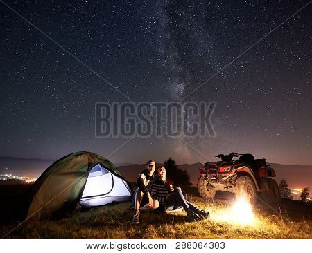 Young Couple Man And Woman Trevelers Sitting Near Glowing Tourist Tent, Burning Campfire, Atv Quad M