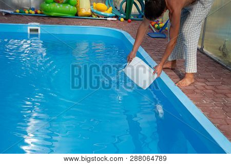 Mens Hands Pour Light Liquid From A Plastic Tank Into A Pool, Into Water. Chemical Water Purificatio