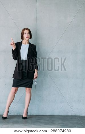 Beautiful young woman pointing up. Confident business colleague. Superior and inquisitive look. Copy space. poster