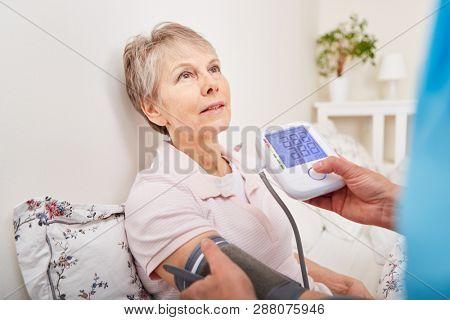 Blood pressure meter controls senior woman's blood pressure