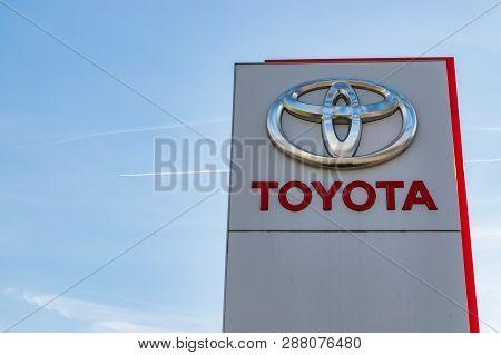 Mouscron,belgium-february 17,2019: Toyota Brand Logo On A Blue Sky Background.toyota Motor Corporati