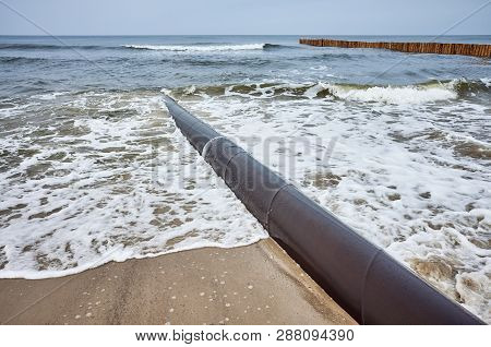 Picture Of A Rusty Pipeline On A Beach.