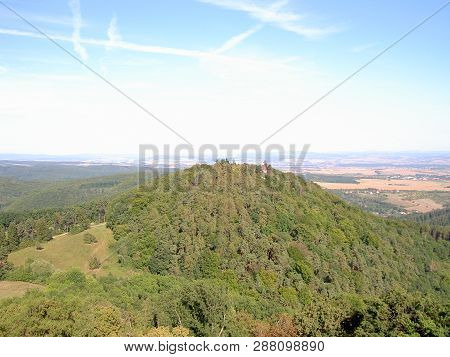 Wooded hill with a turret from above, in the background are forests, meadows, fields, villages and towns, image poster