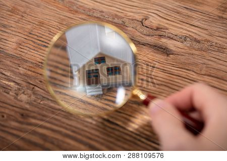 Person Holding Magnifying Glass Over House Model