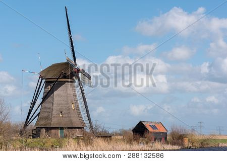 Kinderdijk, Netherlands - March 23, 2016 : Landscape With A Windmill Against Blue Sky And White Clou