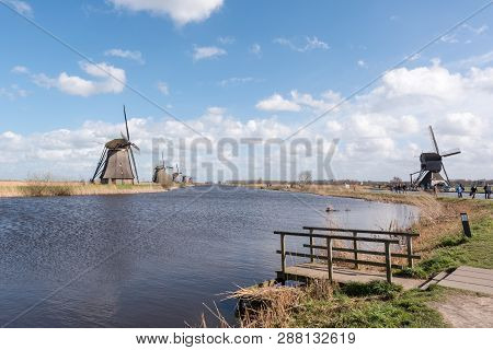 Kinderdijk, Netherlands - March 23, 2016 : Landscape With Windmills Against Blue Sky And White Cloud