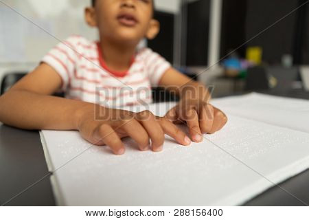Front view of mixed-race blind schoolboy hands reading a braille book in classroom at elementary school