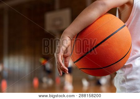 Mid section of a mixed-race schoolboy with a basketball under his arm standing in basketball court at school