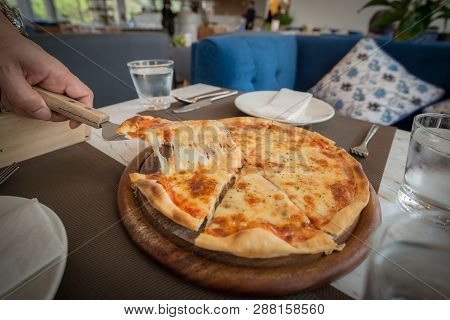 Homemade Pizza On The Wooden Plate And Picked Up By Hand
