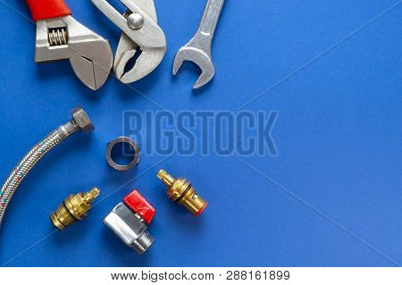 A Set Of Tools For Plumbing, Isolated On A Blue Background With Space For Advertising.