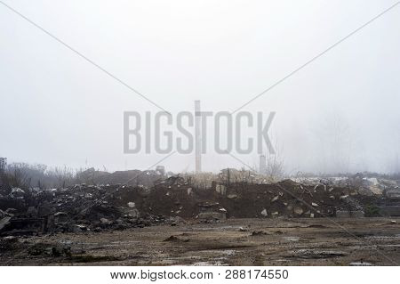 The Remains Of A Large Concrete Building In The Misty Haze In The Form Of Fragments Of Piles And Pil