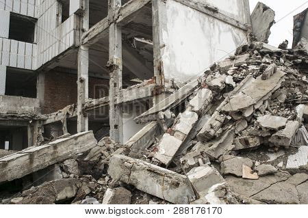 A Huge Pile Of Gray Concrete Debris From Piles And Stones Of The Destroyed Building. The Impact Of T