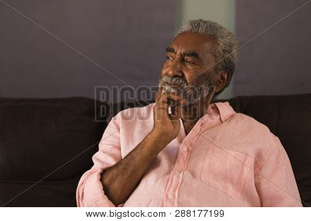 Front view of a thoughtful  African American senior man looking away while relaxing on the sofa in living room at home