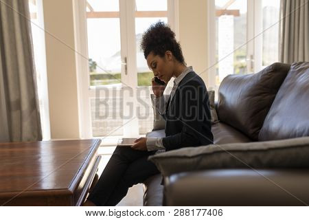 Side view of a female  African American real estate agent talking on mobile phone while using digital tablet on a sofa in living room at home