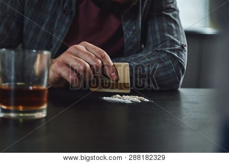 You should just say no to drugs. That will drive the prices down. Man preparing a line of cocaine with a credit card. Close up poster