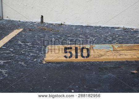 Number 510 Black On Yellow. Asphalt On The Background. Black Number Stencil Painted On Backdrop, Num