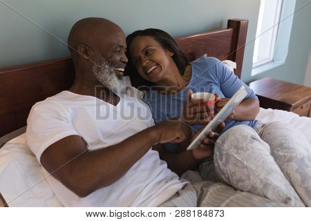 Front view of a happy senior African American couple using digital tablet and drinking coffee in bedroom at home