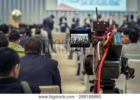 Closeup Video Recording The Speaker With Formal Suit On The Stage Over Rear View Of Audience In The