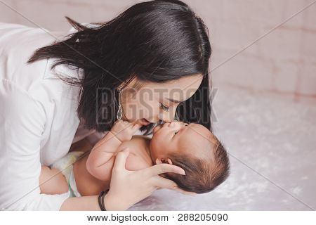 Young Mother And Child On Bed. Mom And Baby Boy In Diaper Playing In Bedroom. Parent And Little Kid