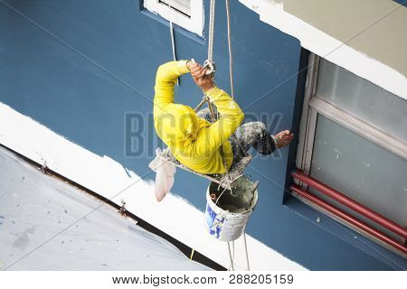 Painters Hanging On Roll, Painting Color On Building Wall. Young Painting Facade Builder Worker With