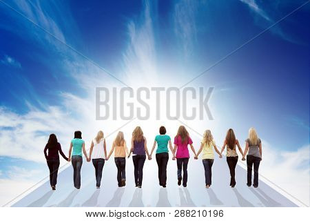 Ten young women walking hand in hand towards a bright blue sky. International women's day, March 8. Female friendship, teamwork and support concept.
