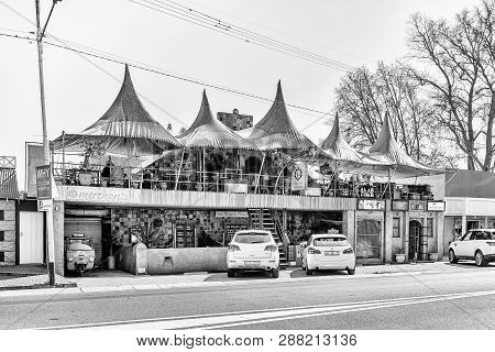 Parys, South Africa, August 2, 2018: A Street Scene With Restaurant, Other Shops And Vehicles, In Pa