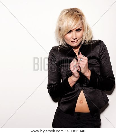 Sexy blonde woman dressed in slacksuit pulling the lapels over her breasts while showing her belly button.