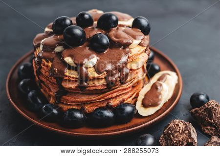 Pancakes With Banana, Chocolate Sauce And Grapes In Plate, On Dark Background.