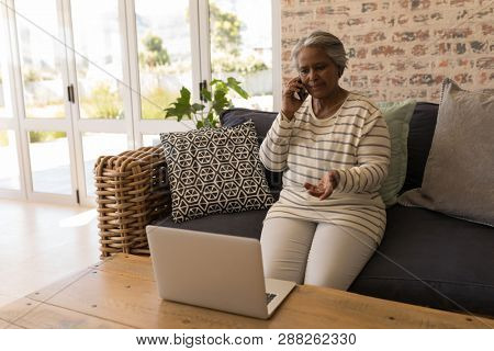 Front view of an active senior  African American woman talking on mobile phone and sitting on a sofa in living room at home