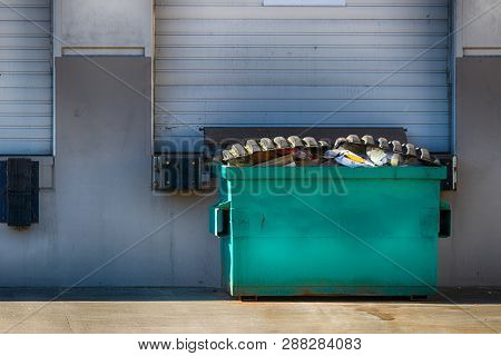 Warehouse Exterior Wall With Garage Door And Dumpster In Daylight