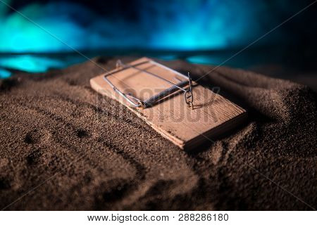 Creative concept. Artwork decoration of mousetrap in sand on dark toned foggy background. Mousetrap captured a man. Selective focus poster