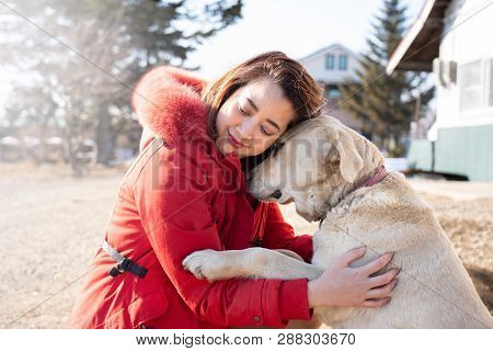 Portrait Of Tender Smiling Beautiful Asian Woman Hugging Her Pet Dog Labrador Retriever In Winter On