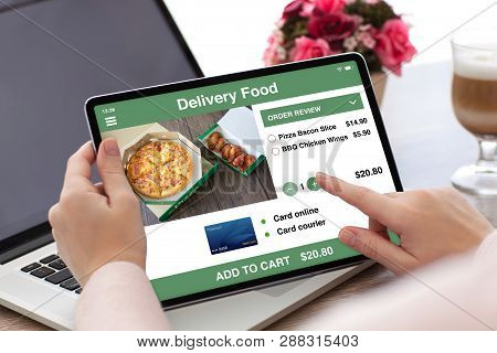 Woman Hands Holding Tablet Computer With App Delivery Food On The Screen And Laptop