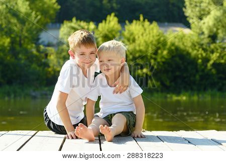 Two Little Boys Sit In An Embrace On The Banks Of The River. Concept Of Friendship And Fraternity.