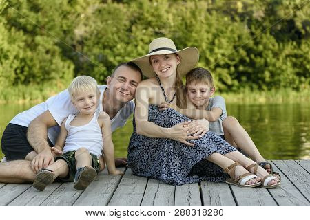 Happy Young Family, Father Mother And Two Little Sons Are Sitting On The River Pier.