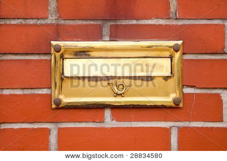 Old golden post box located on brick wall