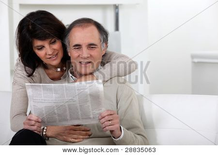 Mature couple reading a newspaper